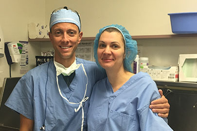 Anne Peled, MD and her husband, Ziv Peled, MD standing in the OR
