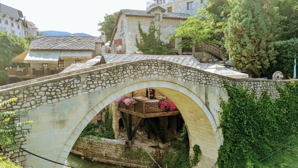 Crooked Bridge bathed in sunlight with cafes in the background is a reason to visit Mostar