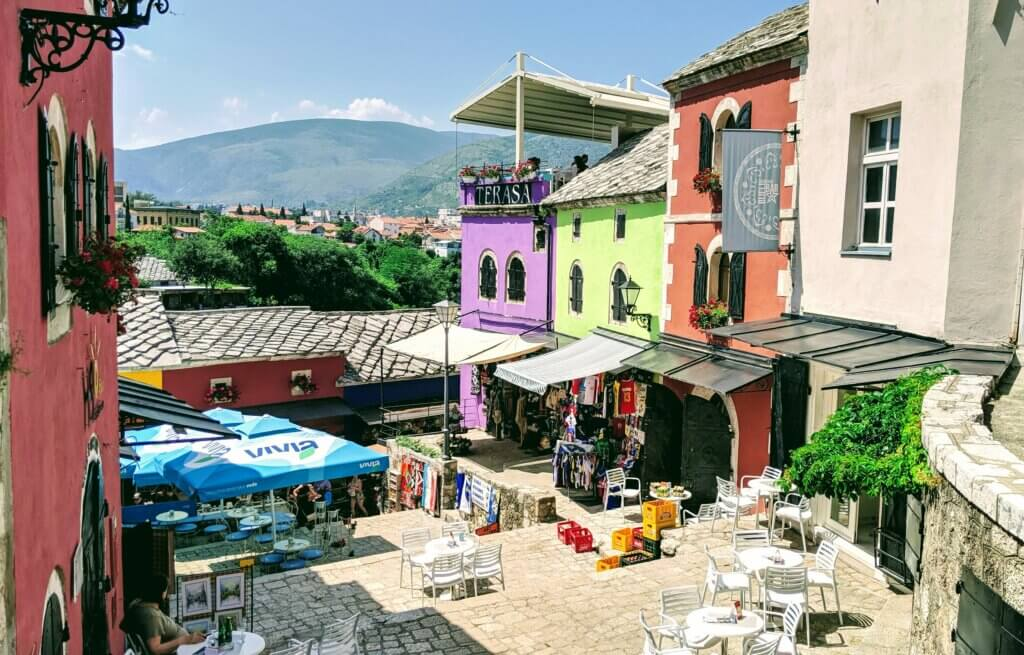Colorful Old Town Mostar with mountains in the background.