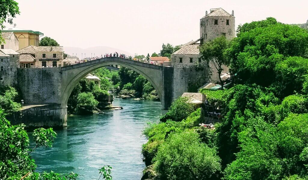 The sand colored Old Bridge in Mostar stands over the beautiful turquoise river.  It is the star attraction and the number one thing to see in the city.