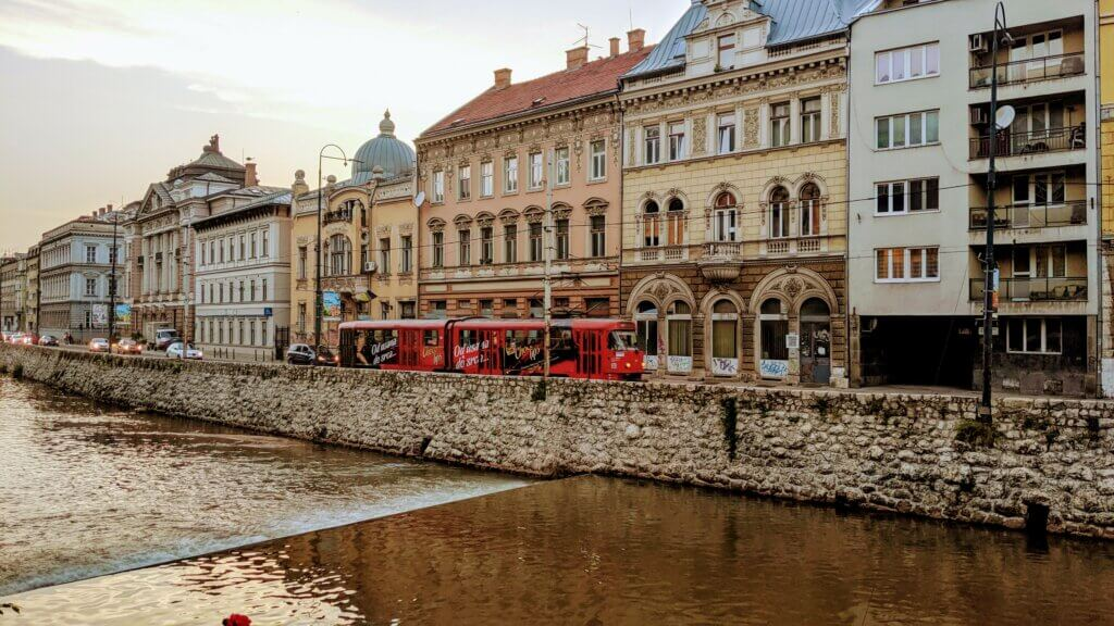Sarajevo along the River Miljacka with a red tram in front of some buildings