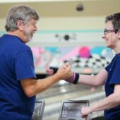 volunteer and participant at bowling celebrating a win
