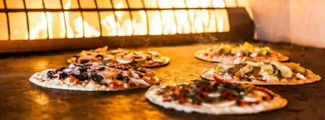 A look into their amazing pizza oven. Photo courtesy Pizza Rev.