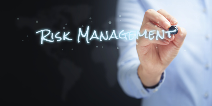 Person writing words risk management