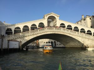 Photo of Rialto Bridge in Venice, Italy, with a water taxi passing under