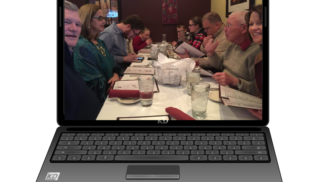 Laptop screen displaying people having fun eating together