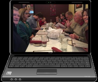 Laptop screen displaying people having fun eating together