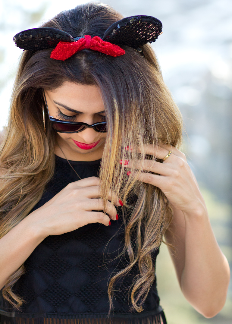 A Candid Photo of Alexis Alcala Adjusting Her Hair and Minnie Mouse Ears as She Prepares for a Photo in Front of the Matterhorn at Disneyland