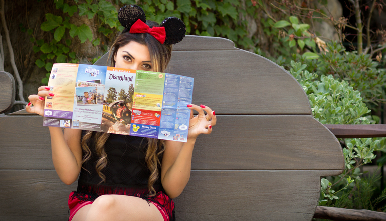 Alexis Alcala Hiding Behind a Map of Disneyland in Critter Country