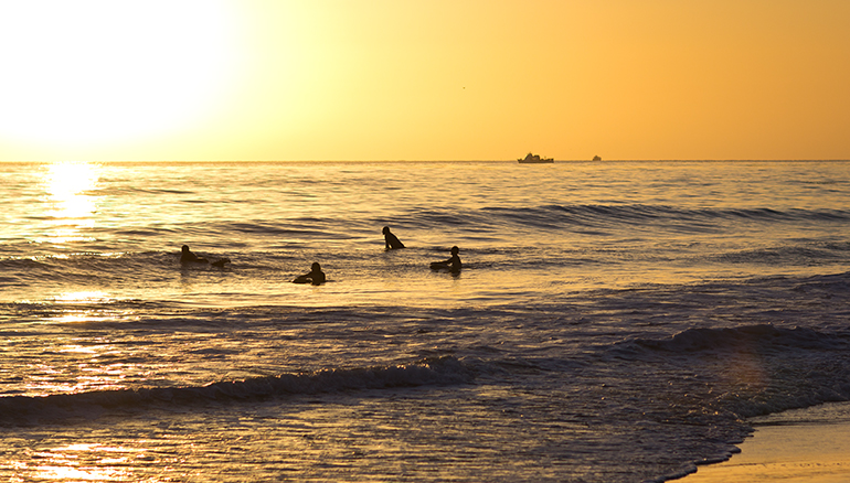 A View of Surfers in the Pacific Ocean Off the Coast of Dana Point, California During Sunset
