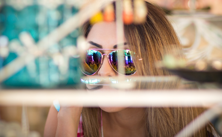 A Candid Photograph of Alexis Alcala Trying on Fashionable Sunglasses at a Small Boutique Store in Laguna Beach, California