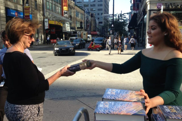 Woman handing out books to people on street