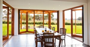 Multiple sets oof bifold patio doors leading from a dining area to an expansive backyard