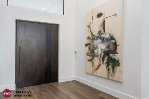 Large, brown pivot entrance door in home's entryway next to a painting
