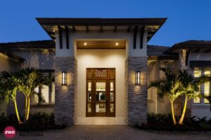 Swinging entry doors highlighted by outdoor lights at night
