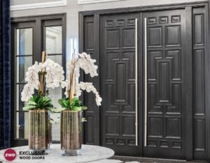 Detailed double swinging entry doors leading to a foyer with a table and orchids