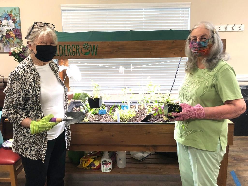 Two retirement community residents gardening indoors.