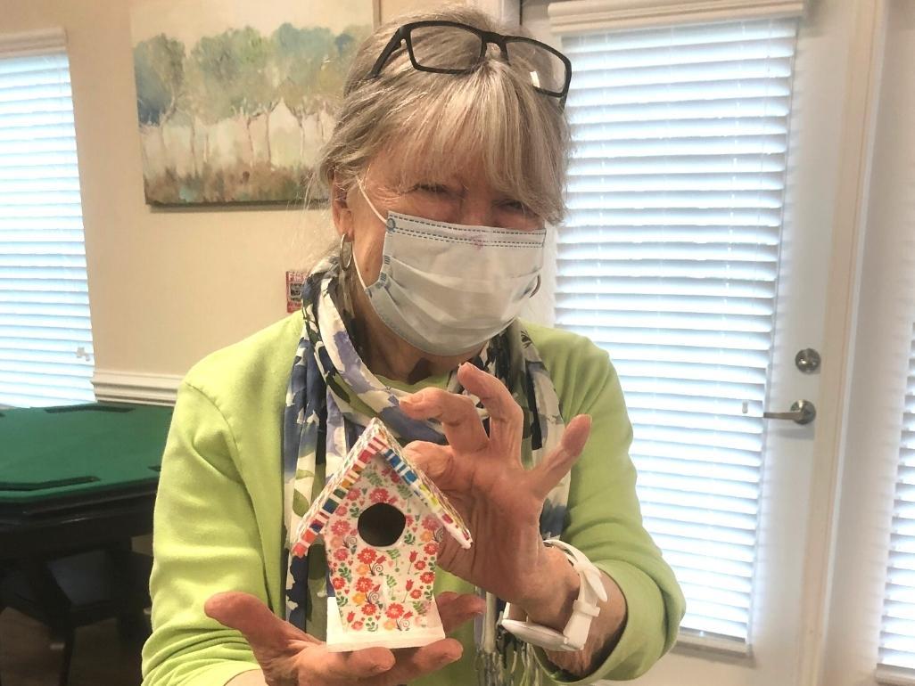 Senior resident showing off her trinicately painted birdhouse key holder.