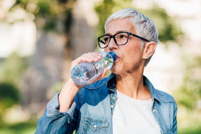 Senior woman drinking water outside to stay hydrated