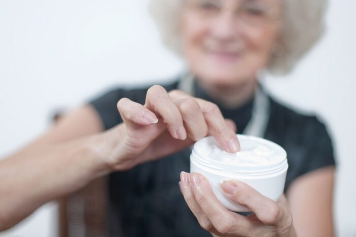 Senior woman scooping lotion out of a container