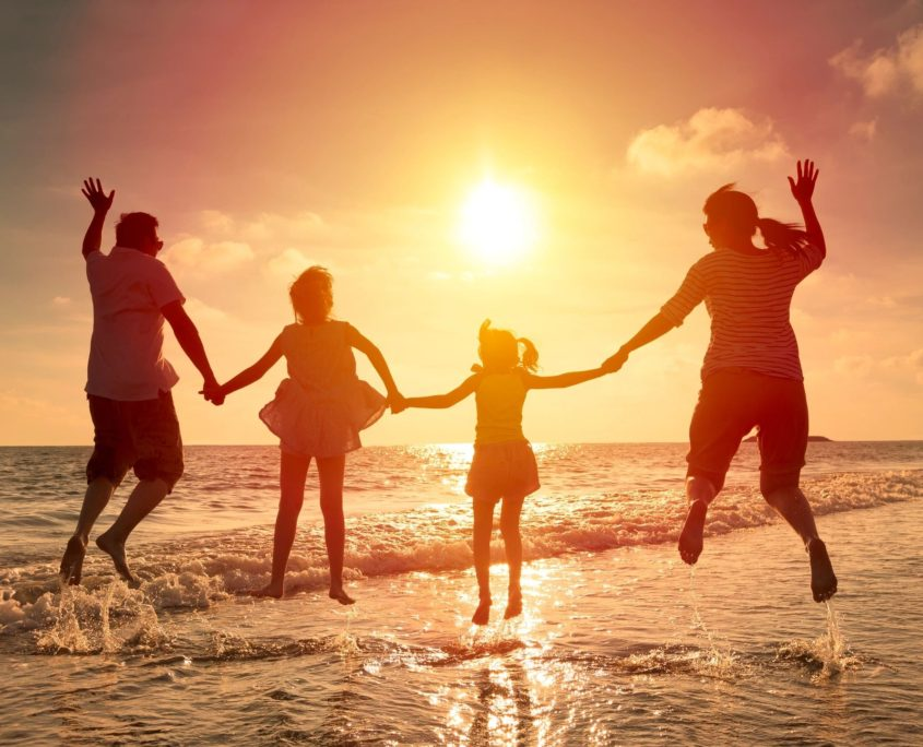 family with life insurance jumping on beach