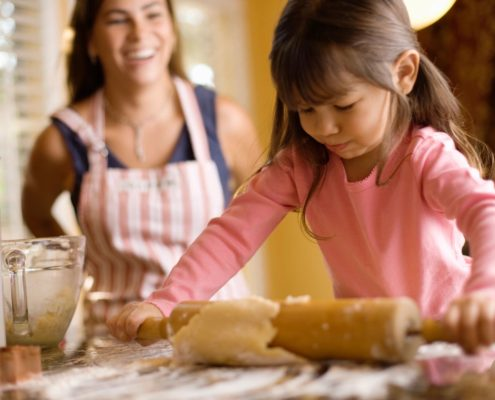 family with umbrella insurance making cookies