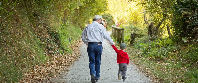 elderly man walking a child
