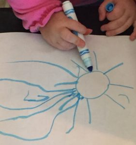 toddler practices drawing to prepare for letter strokes
