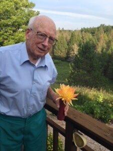 Richard Pollard holding a Dahlia flower.