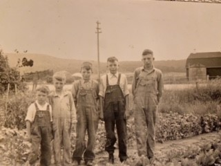 Photo of the five Pollard brothers standing infront of the Pollard Dairy barn.
