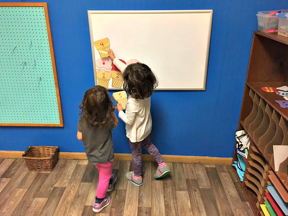 Two preschool children play a number matching  game shaped like ice cream cones on a magnet board. There is a blue wall behind them.