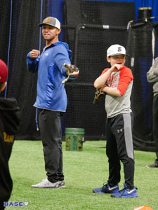 Coach Kai demonstrates a baseball drill with a volunteer.