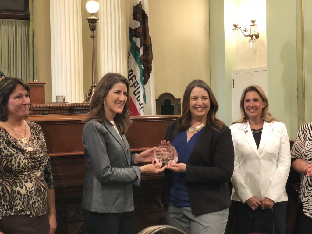 State President Sara Reid Herman presents Assembly member Catharine Baker with the 2018 Cornucopia Award.
