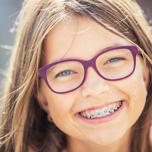 Happy smiling girl with braces and glasses.