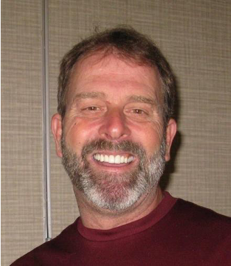 A man with a beard smiling