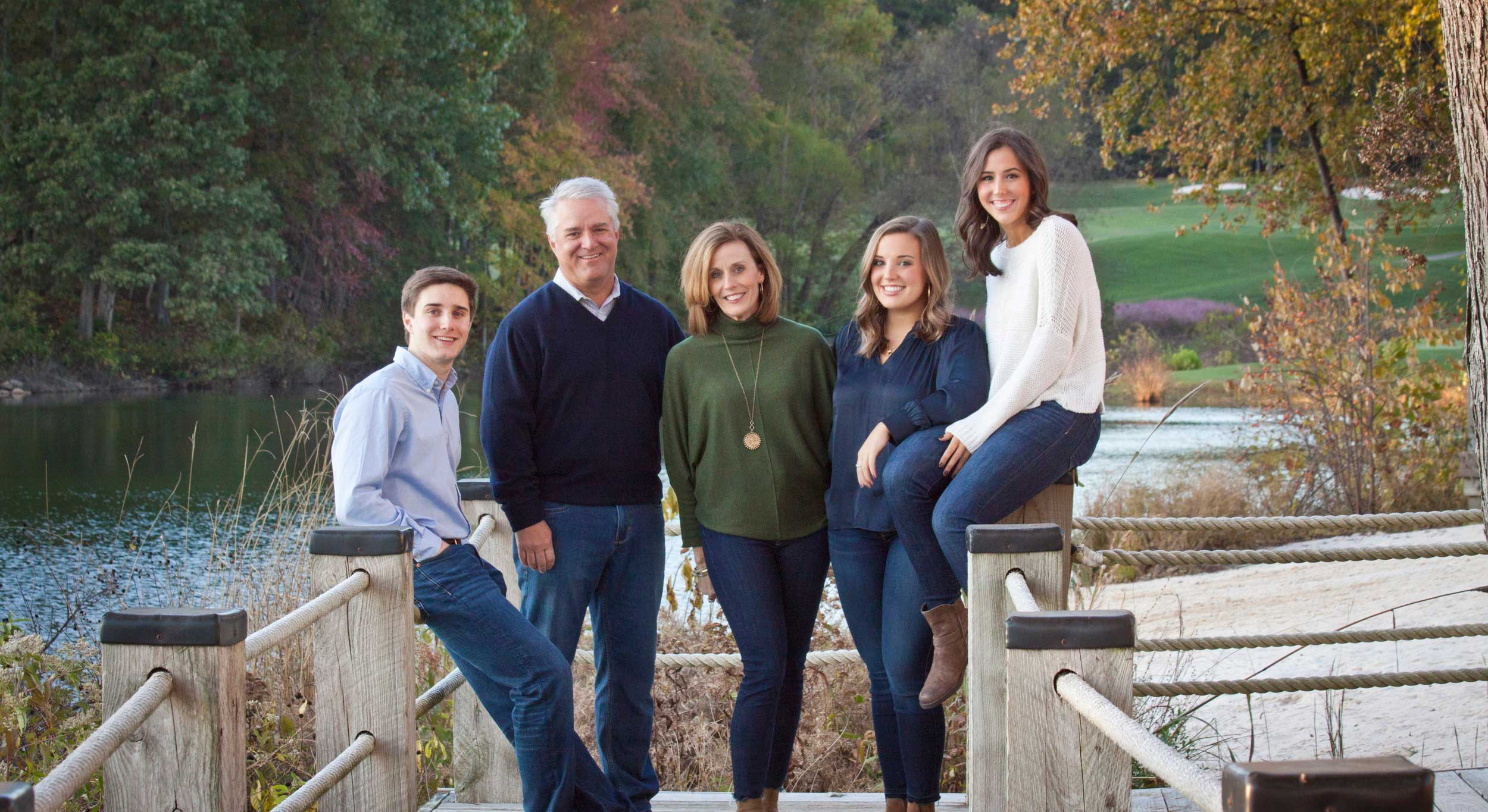 Family on dock in front of greenery at Lake Norman, NC