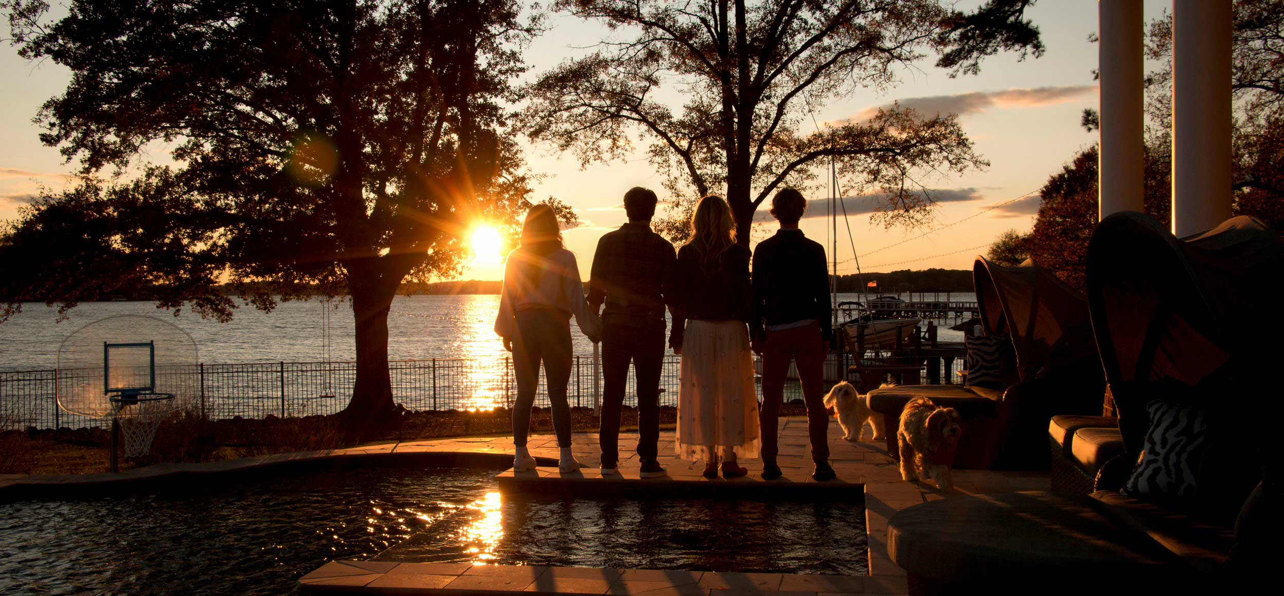 Photo of back of family, facing sunset, outdoors at Lake Norman, NC