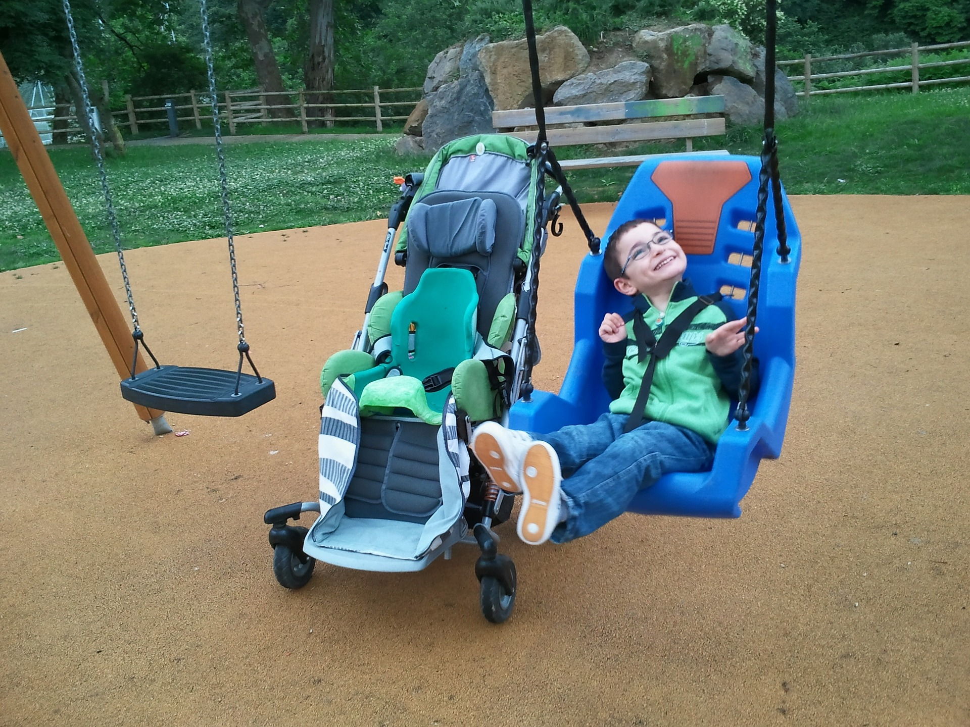 Disabled child smiling in a playground swing