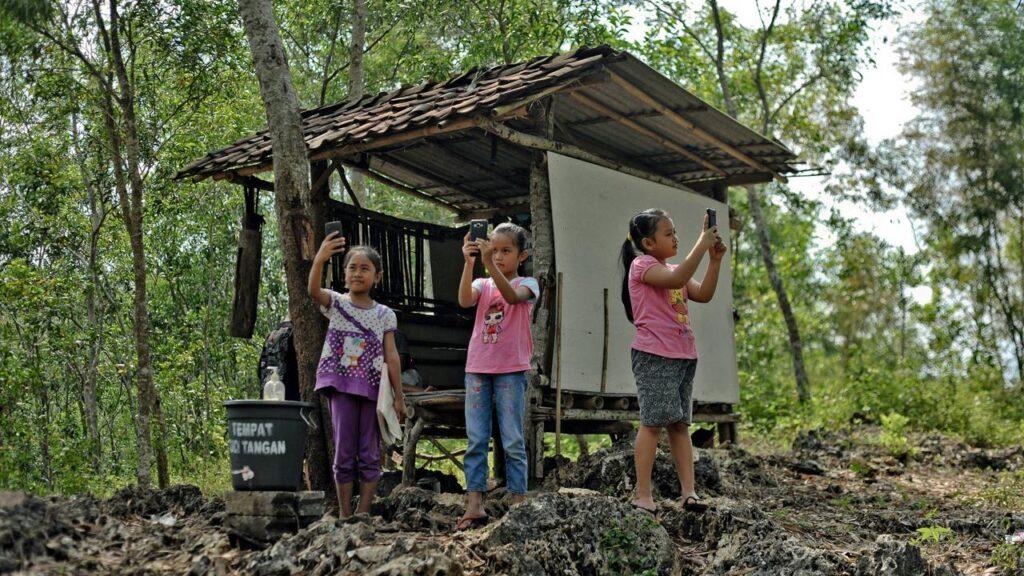 School age students searching for internet signal around Gunung Kidul, Yogyakarta (source photo by Agus Supriyanto / AFP)