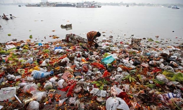 A woman collects items thrown into the Ganges as religious offerings after celebrations marking the last day of the Navratri festival in Kolkata, India. Photograph: Rupak de Chowdhuri/Reuters