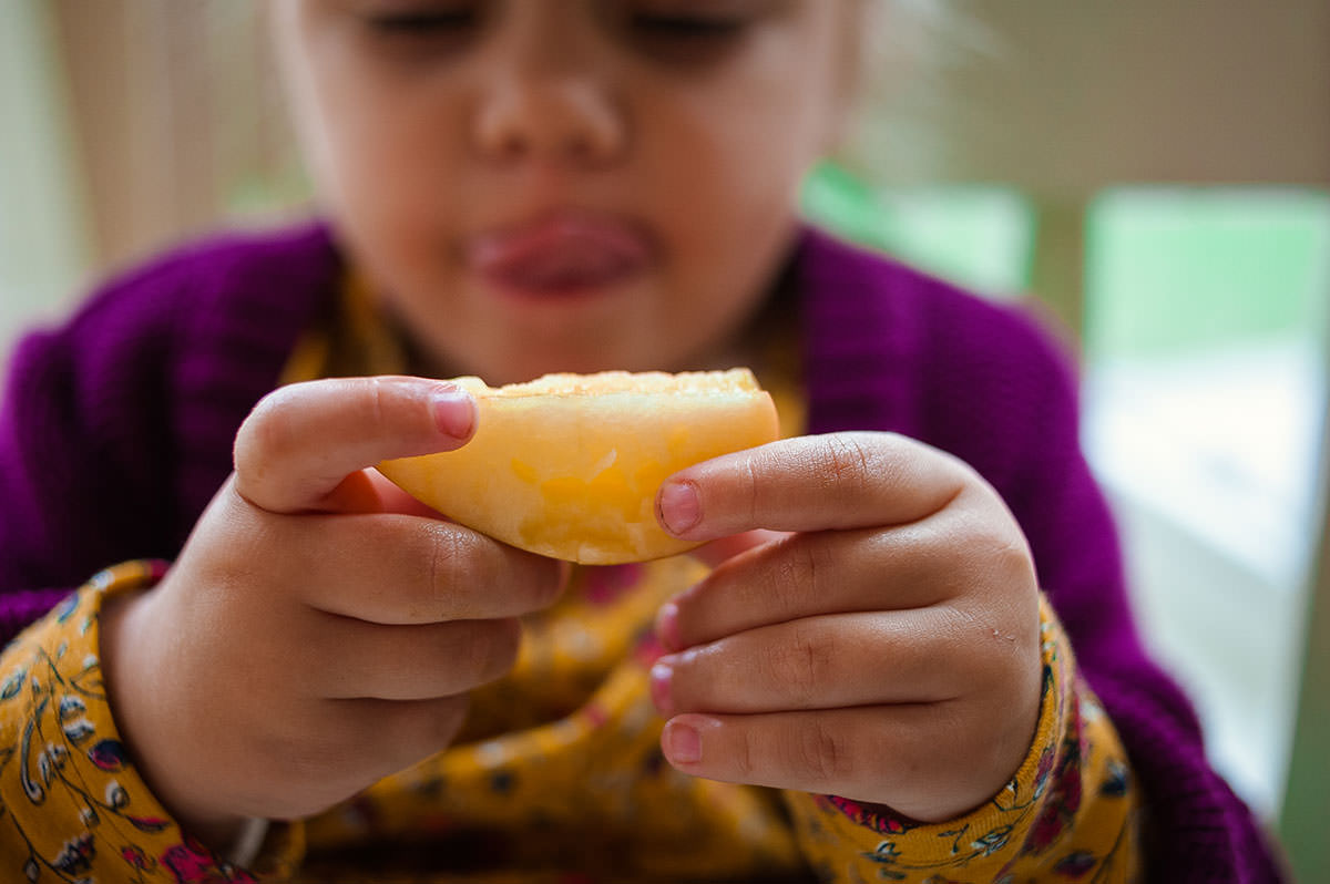 girl licking lips at apple slice