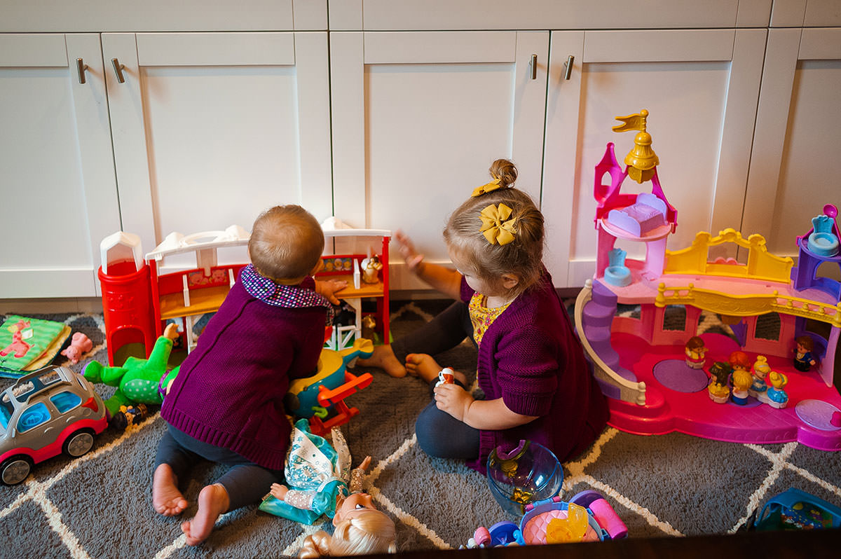 sisters playing with little people house