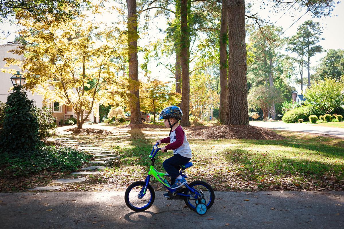 boy riding bike with training wheels