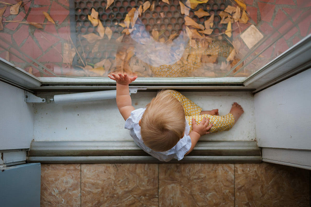 Baby girl looking out storm door with reflection