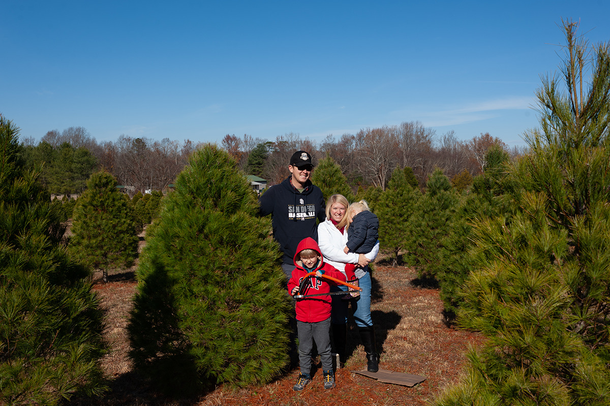 family standing next to their Christmas tree