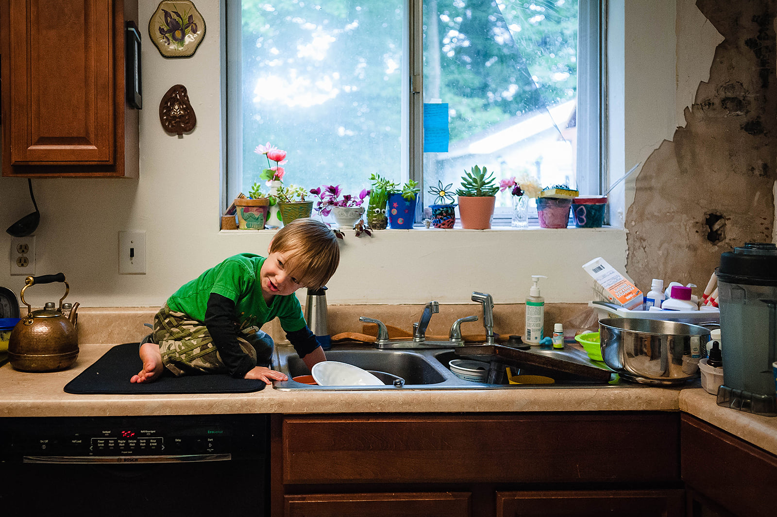 boy getting something out of sink