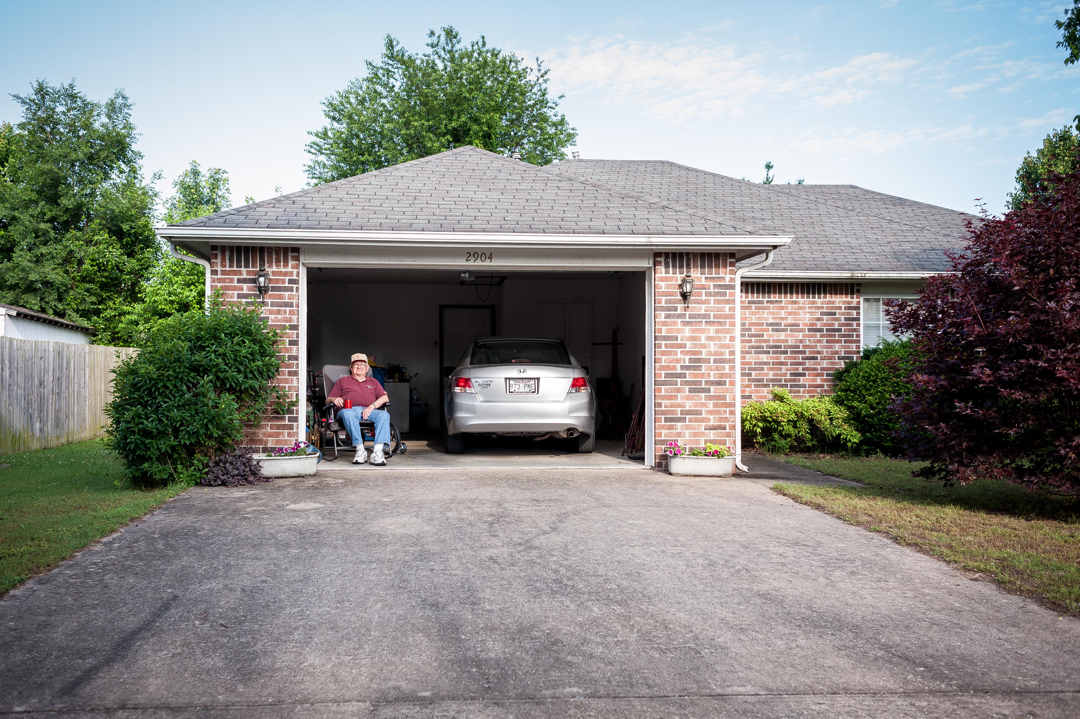 man sitting in chair with garage door open