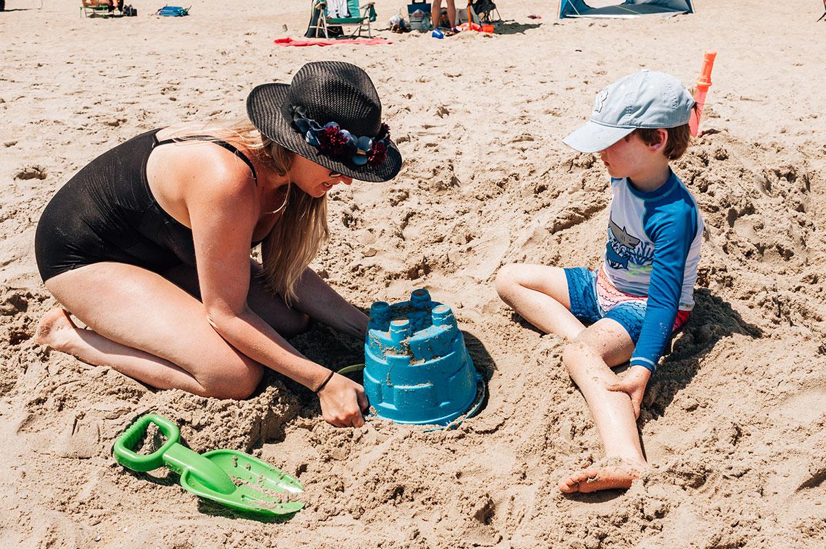 mom helping son build sand castle on the beach
