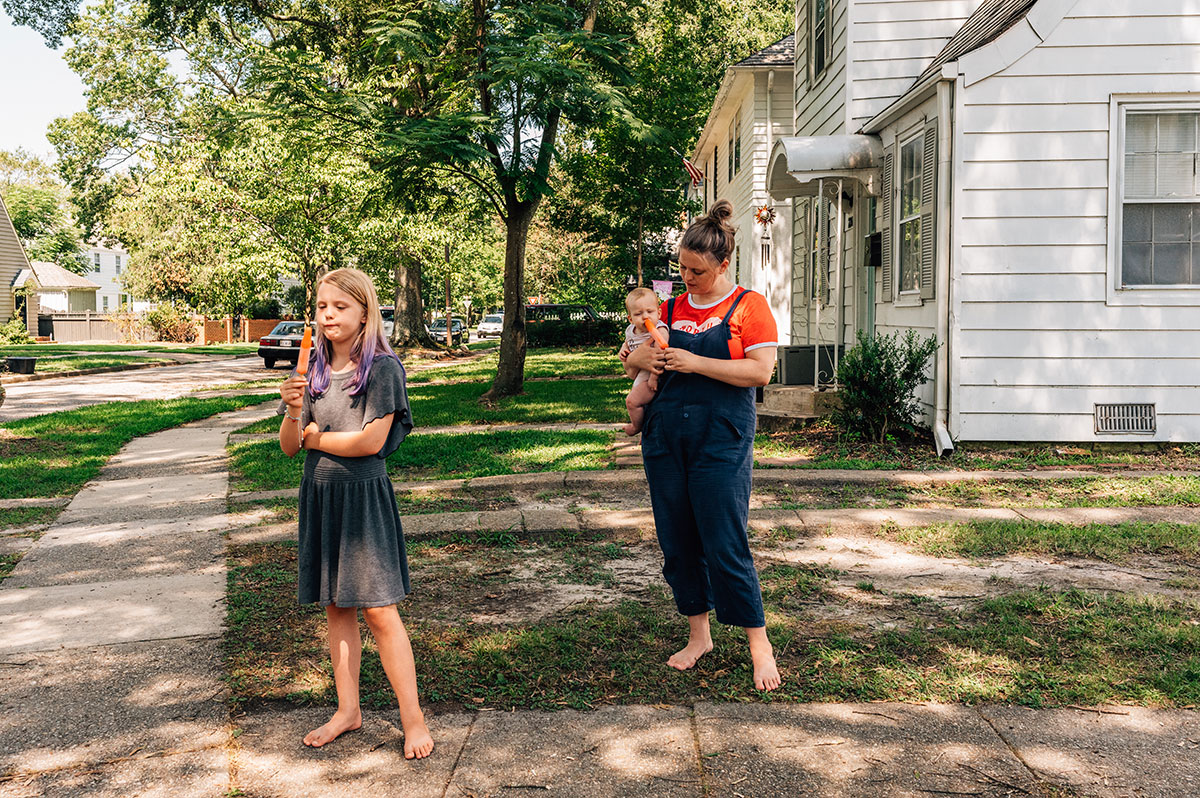 a mother and her children stand outside their home along the sidewalk eating orange popsicles