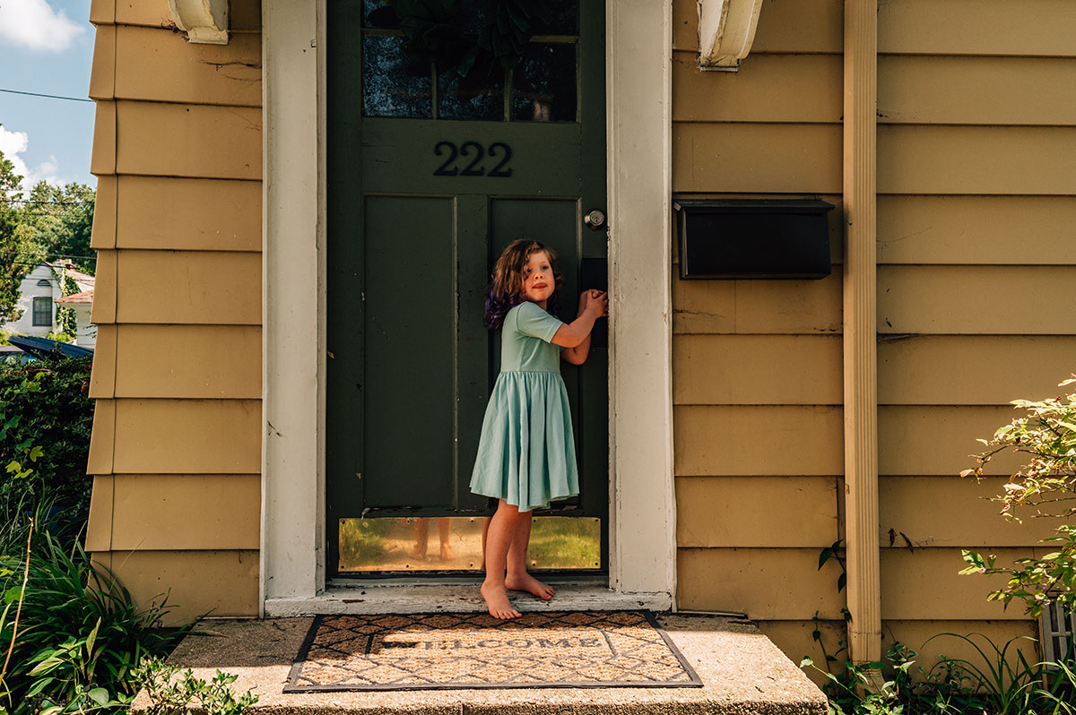 Little Ophelia stands at the front of her door wearing a beautiful aqua a-line dress.
